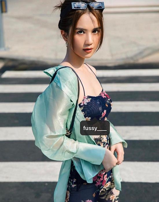 Cụ thể, người đẹpra phố với jumpsuit màu đen họa tiết hoa, chất liệu mỏng tang, mát mẻ, khoác ngoài áo sơ mi voan màu xanh mint.