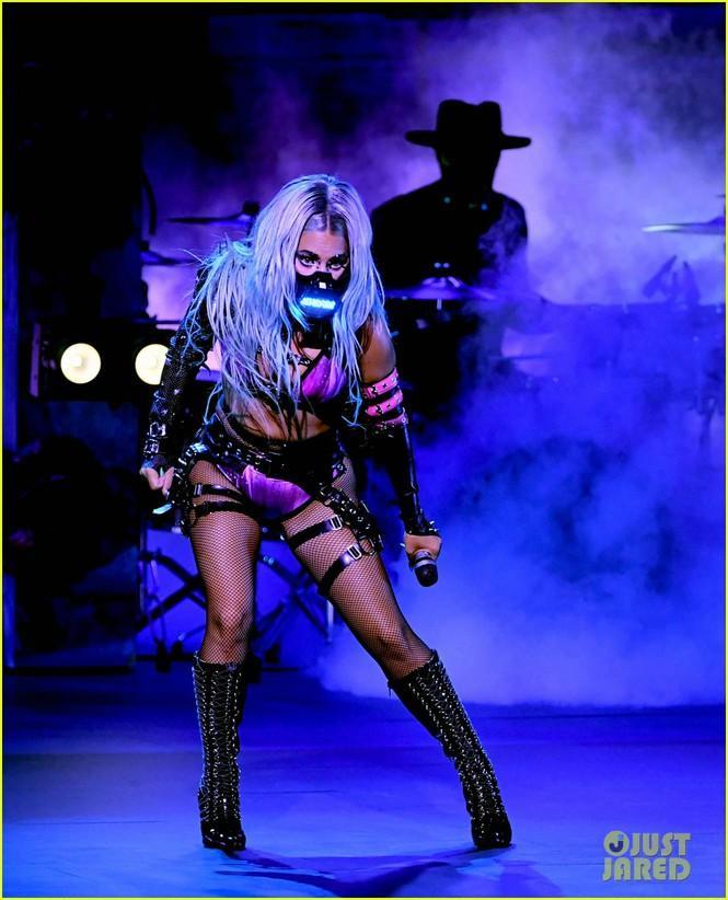 Cô mặc đồ bơi hai mảnh, xung quanh chằng chịt dây da đen, kết hợp tất lưới và boot cao cổ, đầy nổi loạn.